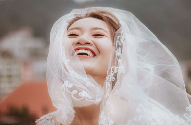 DIY Wedding Makeup - Grinning Bride Wearing Veil
