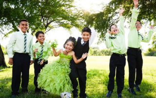 Little Girl Wearing Lime Green Cincoanera Dress And Boys Wearing Matching Green Shirts
